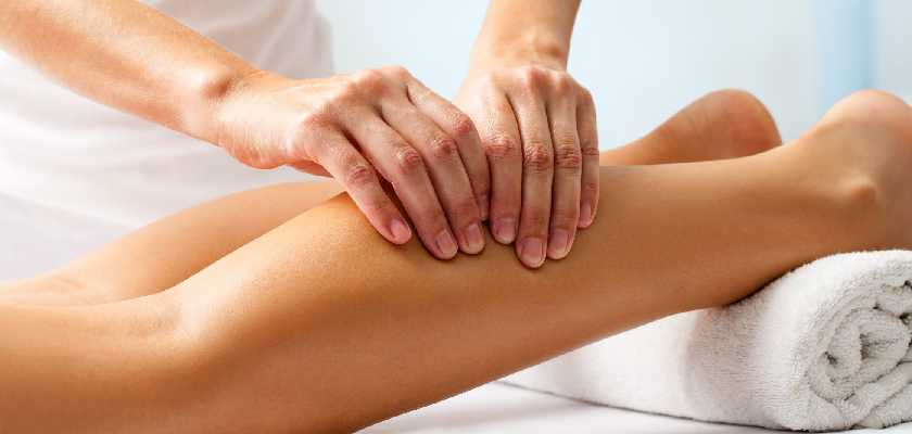 Sportsperson getting a massage done to calf muscle at a massage centre.