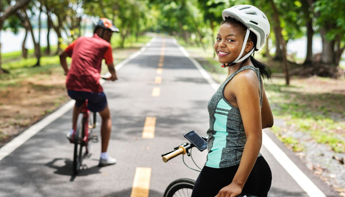 Smiling Woman Starring Towards The Camera With Her Bicycle.